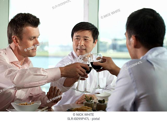 Multi racial businessmen toasting with wine