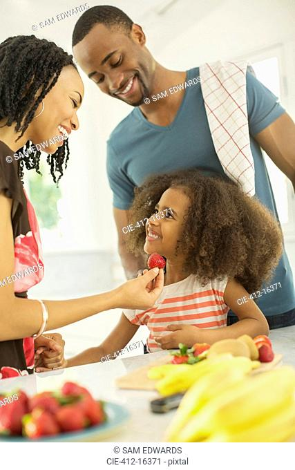 Happy family eating strawberries