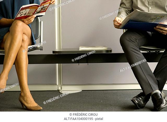 Man and woman sitting in waiting room, low section