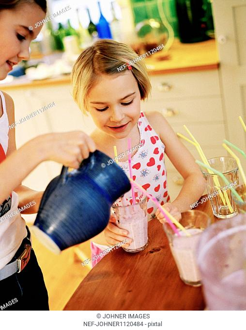 Girls pouring smoothie into glass