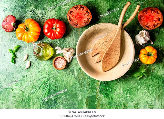 Variety of red and yellow organic tomatoes with olive oil, garlic, salt, empty ceramic bowl, wooden spoons for salad over green texture background