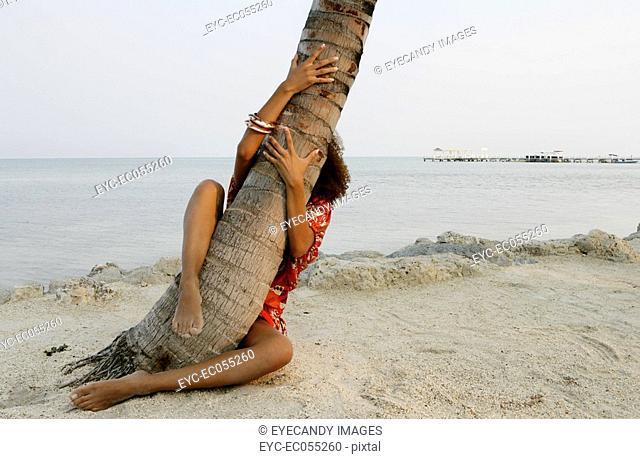 Young woman grabbing palm tree
