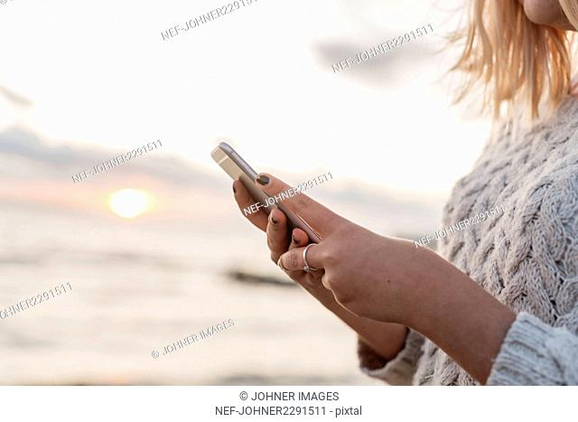 Woman holding smartphone at beach