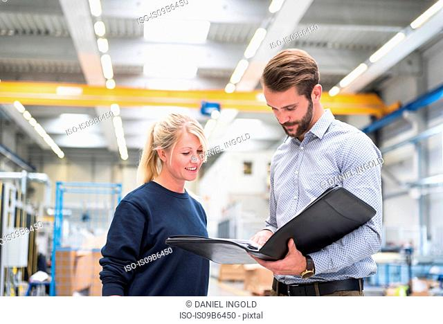 Manager and factory worker looking at paperwork in file