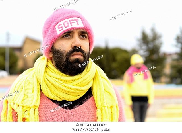 Portrait of bearded gay with nose piercing wearing pink cap with the word 'soft'