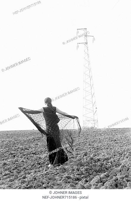 Female model in long dress on a field, Spain