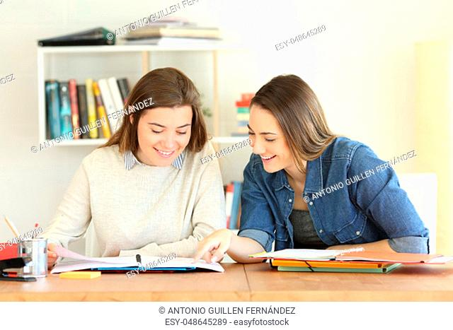 Front view portrait of two happy students studying together helping each other reading notes in a notebook on a table