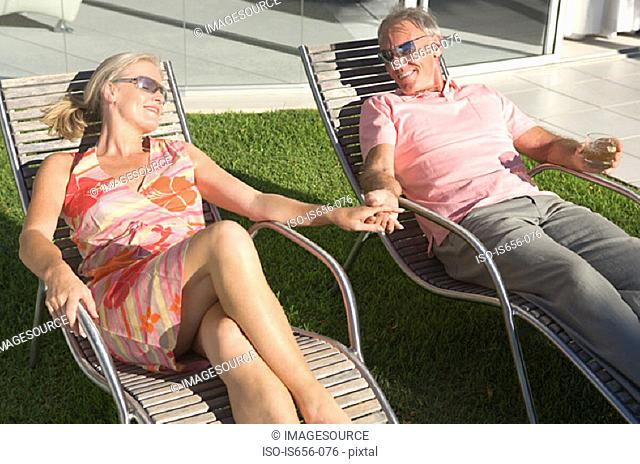 Mature couple in lounge chairs