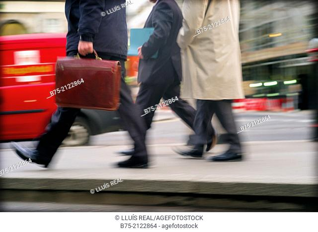 tree unrecognizable executive with portfolio walking hurriedly in the city with traffic in London, England, UK, Europe