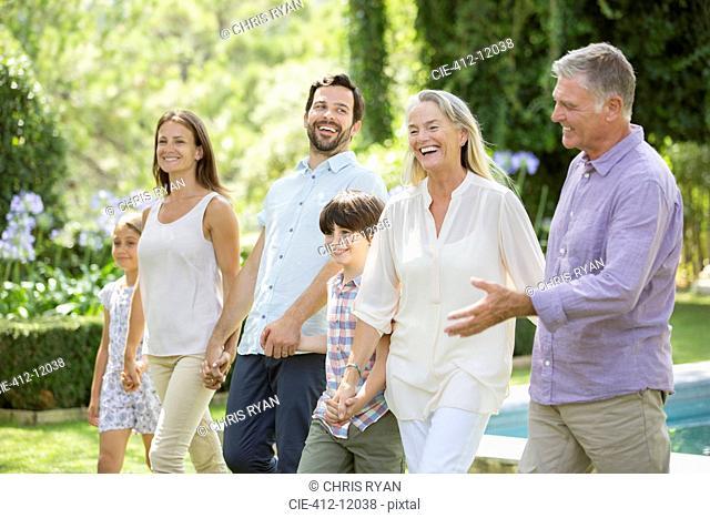 Multi-generation family walking in backyard
