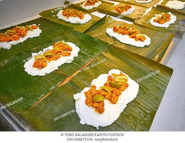 Tamale preparation Mexican recipe with banana leaves and cornmeal