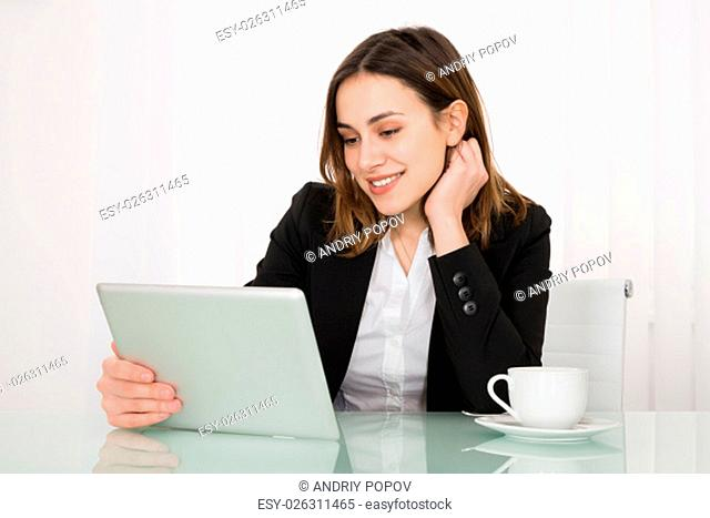 Happy Young Businesswoman Holding Digital Tablet On Desk In Office