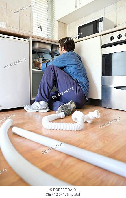 Plumber working on pipes under sink