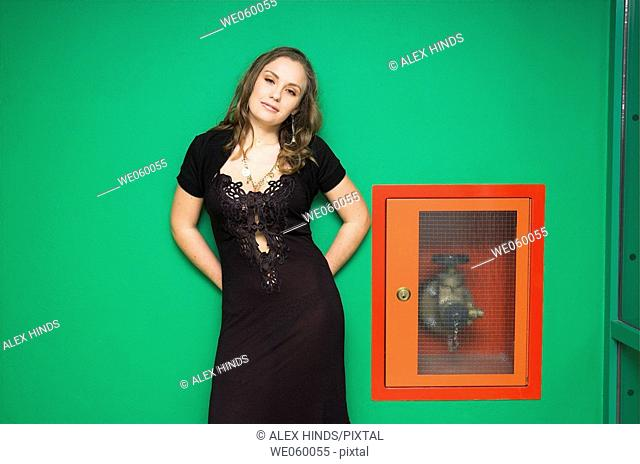 Young female fashion model posing against a green wall and fire hydrant
