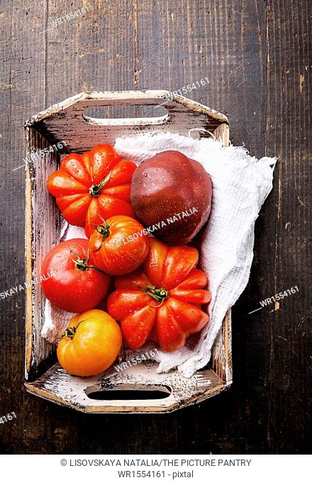 Ripe fresh colorful tomatoes in wooden box on dark wooden background