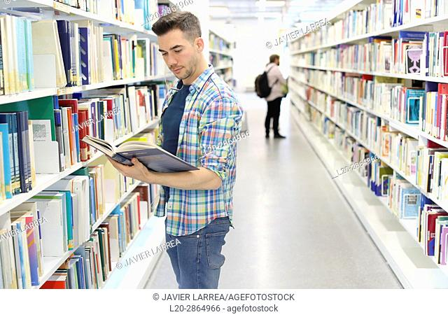 Student with book in library, University of the Basque Country, Donostia, Gipuzkoa, Spain