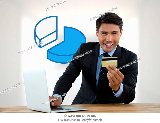 Businessman with laptop at desk with diagram of pie chart and bank card