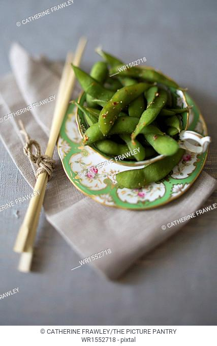 Tea cup of chilli edamame with chop sticks