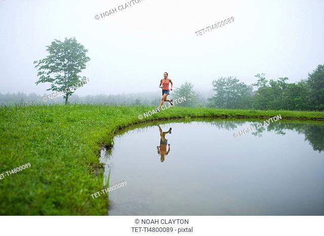 USA, Vermont, Landgrove, Woman jogging by lake