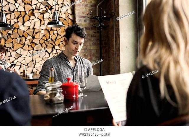 Man with female friends reading menu at table in restaurant