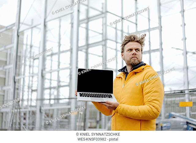 Man holding laptop, construction site in the background