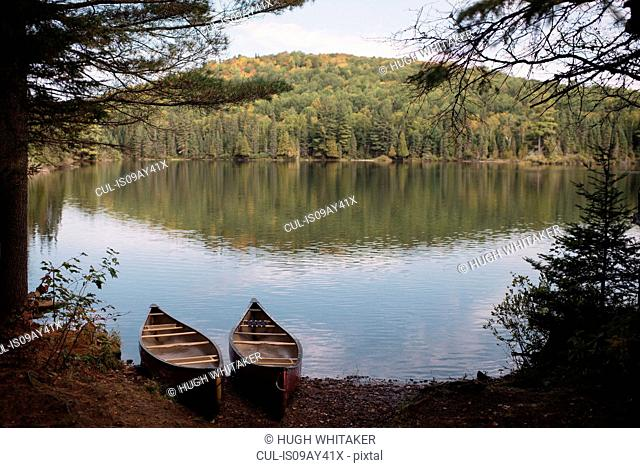 Two canoes at waters edge, Algonquin, Ontario, Canada