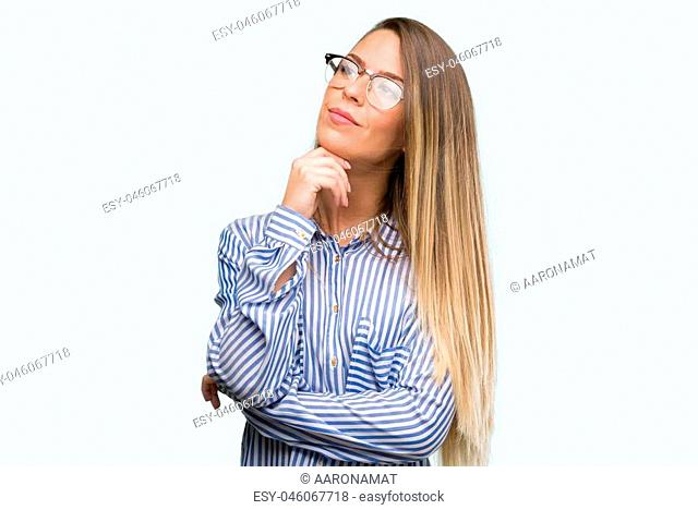 Beautiful young woman wearing elegant shirt and glasses with hand on chin thinking about question, pensive expression. Smiling with thoughtful face