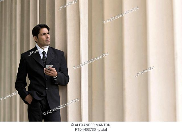 Businessman with mobile phone and hand in pocket