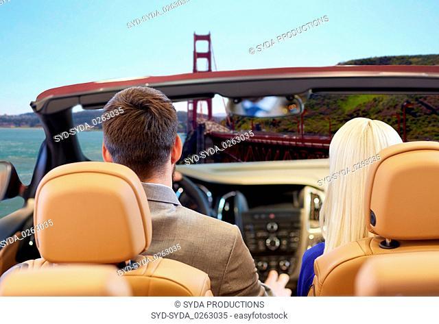 couple driving in car over golden gate bridge