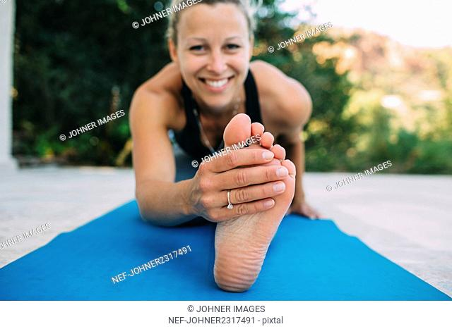 Young woman exercising on veranda