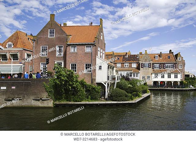 Enkhuizen, small city of northern holland, historic buildings on the bank of the channel, under a blue sky with clouds
