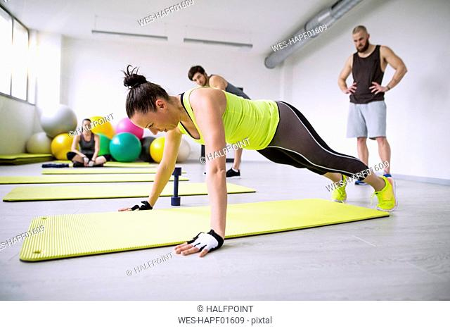 Woman exercising in gym watched by training partners