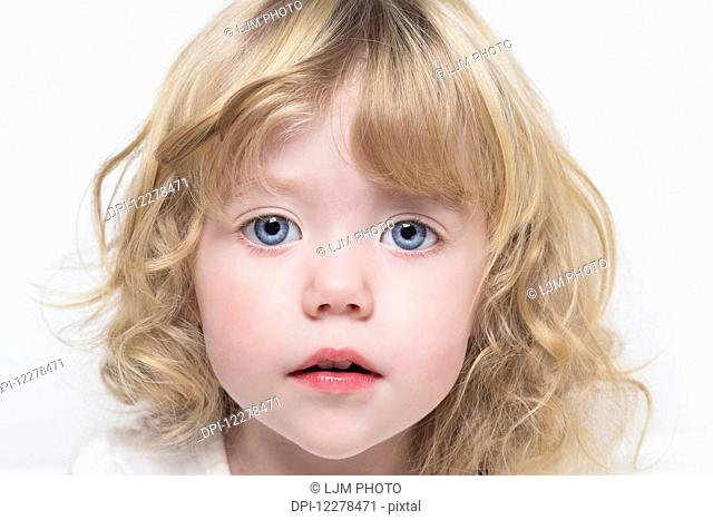 Close up of a toddler with beautiful big blue eyes and blond curly hair; Spruce Grove, Alberta, Canada