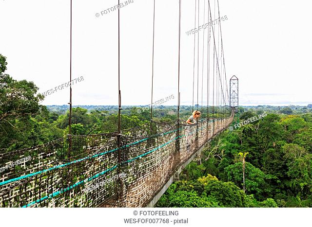 Ecuador, Amazon River region, tourist on suspension bridge above rain forest