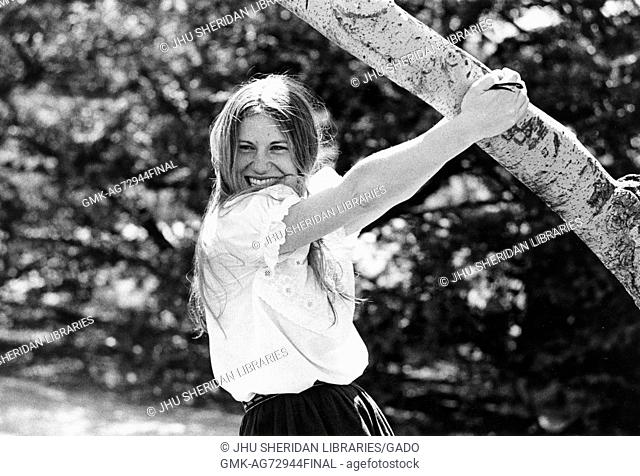 A photograph of a female undergraduate student at Johns Hopkins University hanging off of a tree on campus during the first years of the undergraduate program's...