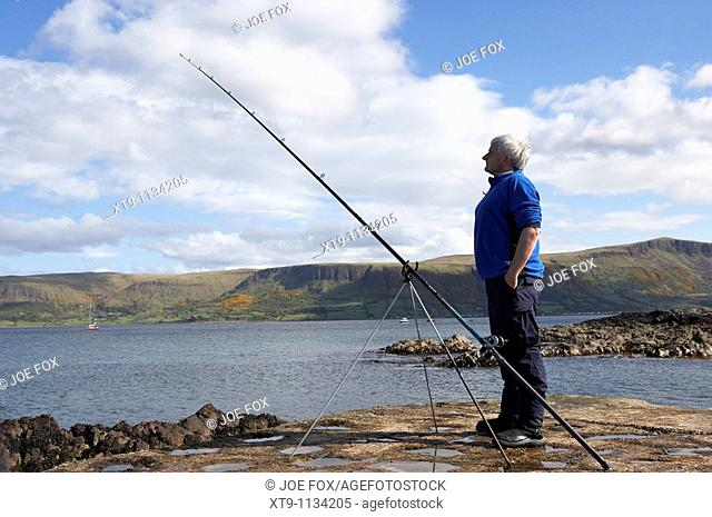 middle aged man fishing with rod and line on the county antrim coast northern ireland uk