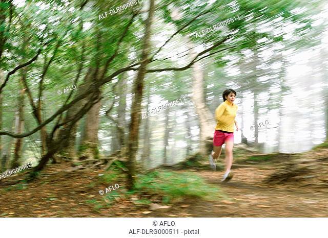 Young Japanese woman trail running at Mount Daibosatsu, Yamanashi Prefecture, Japan