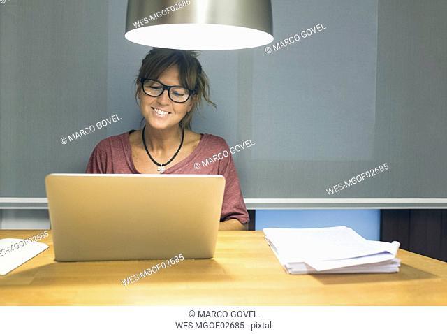 Smiling woman using laptop at desk