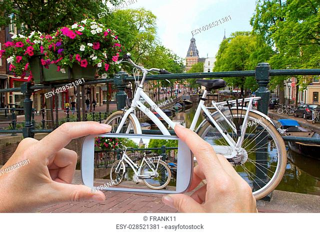 In the left bottom of the photo are hands holding smart phone and taking picture of a white bicycle standing on the bridge in Amsterdam (Netherlands)