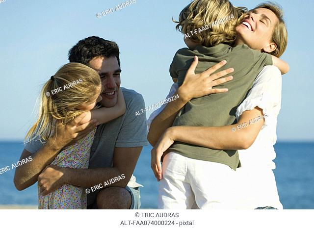 Parents embracing children at the beach