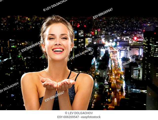 people, holidays, advertisement and luxury concept - laughing woman in evening dress holding something imaginary over night city background