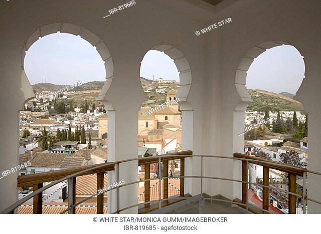View through the arches of the mosque minaret onto the El Albayzín or Albaicín quarter of Granada, Andalusia, Spain