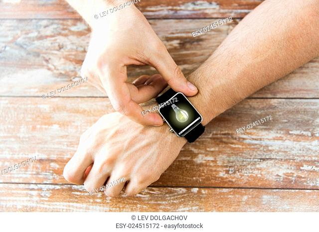 business, modern technology, startup, idea and people concept - close up of male hands setting smart watch with light bulb on screen on wooden table