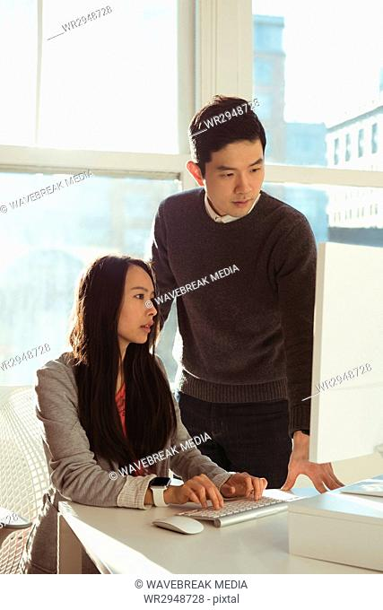 Male and female executives discussing over computer at desk