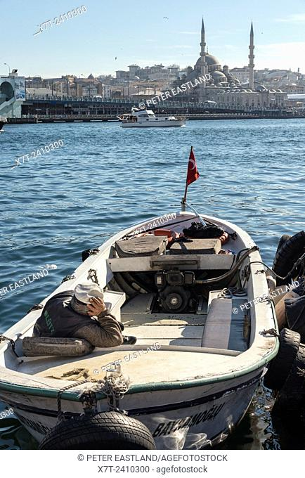 A boatman surveys the scene from Karakoy waterfront across the Golden Horn toward the Yeni mosque at Eminonu and the Istanbul skyline