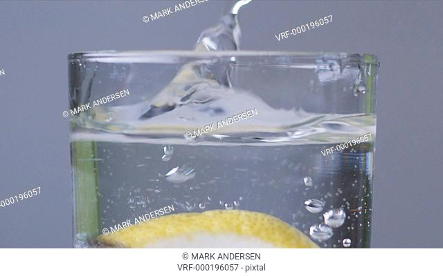 dropping a lemon slice into a glass of water