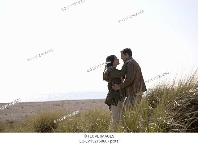 A pregnant woman and her partner standing amongst the sand dunes, hugging