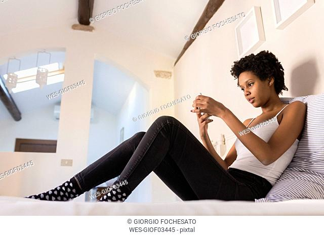 Young woman using cell phone in bedroom