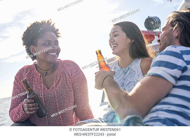 Happy friends on a boat trip having a beer