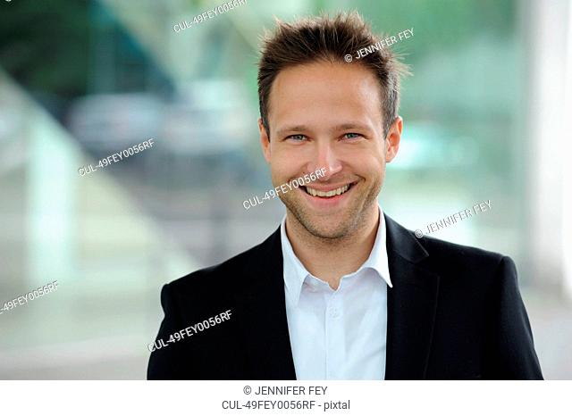 Smiling businessman standing at window
